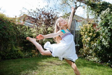 little girl dancing in garden