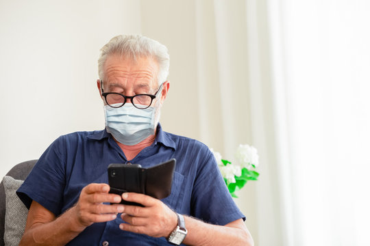 Elder following Coronavirus(Covid-19) outbreak news intentionally via mobile phone and self protection by wearing disposal face mask while stay at home.