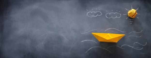 banner of single paper boat over blackboard background