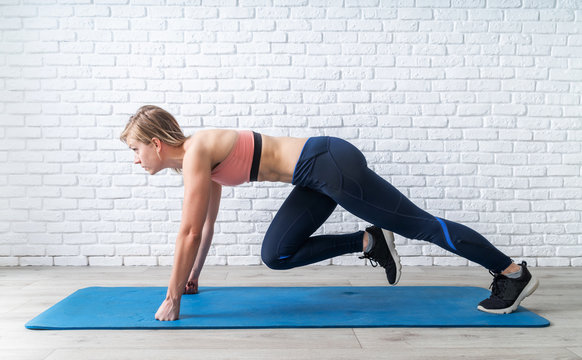 Young sportive woman doing mountain climber exercise at home