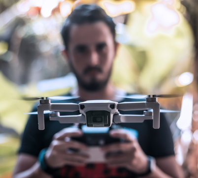 Front closure of the Mavic Mini drone flying over a person who controls it with his remote control