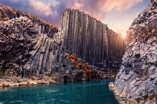 Amazing Nature landscape of Iceland. Impressively beautiful Studlagil canyon with basalt columns and colorful sky during sunset. Tipical Iceland scenery. Iconic location for photographers and bloggers