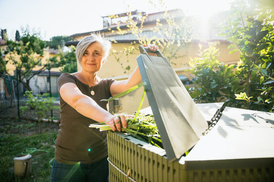 Portrait of an adult woman in her home garden while throwing organic waste in the compost bin - Concept of recycling and sustainability