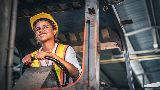 Female factory worker operating forklift in warehouse.
