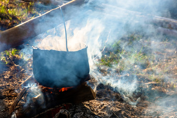 steaming old pot outdoor. cooking and camping. outdoor adventures concept. beaten cauldron on camp fire