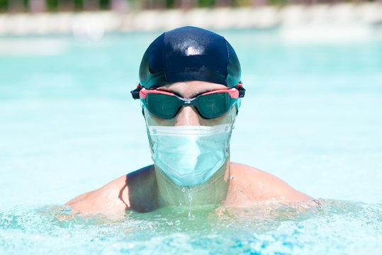 Masked man swimming, coronavirus pandemic sport concept