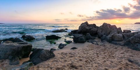 idyllic sunset on the sea shore. waves crashing rocks on sandy beach. beautiful cloudscape above the horizon