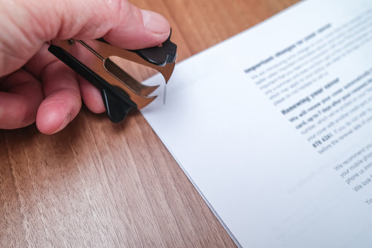 Close up of human hand using a staple remover to remove a staple from sheets of paper on a wooden desk in a commercial office