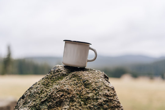 White enamel cup placed on a rock. Close up photo of a metal camping mug on a stone with blurred background.