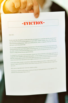 Someone serving an Eviction Notice with hands in view - Late Rent - Late Mortgage - Payment - Concept