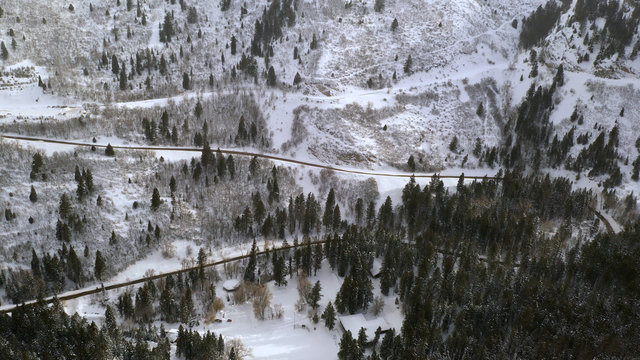 Aerial view of road winding up winter landscape in mountains through American Fork Canyon in Utah.