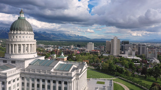 Aerial view flying over the Capitol Building towards downtown Salt Lake City Utah viewing the Wasatch Mountains.