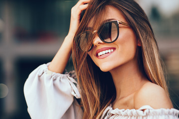Portrait of a beautiful young woman with smile and sunglasses in the city