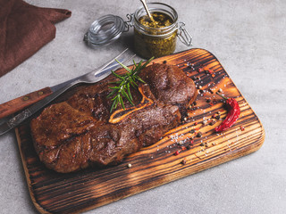 Fototapete - grilled beef steak with bone on a cutting board spices