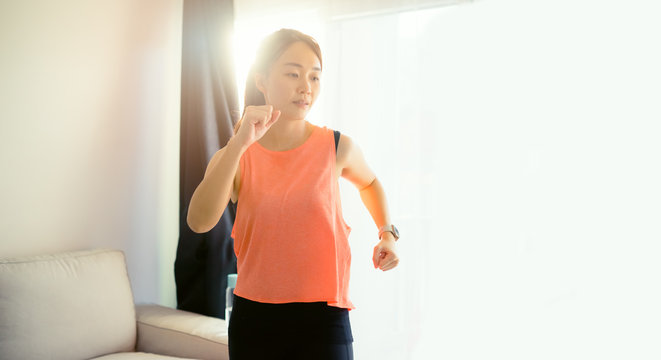 Video streaming Stay home.Home fitness workout class live streaming online.Asian woman doing strength training cardio aerobic run exercises live teach video on a camera in the living room at home.