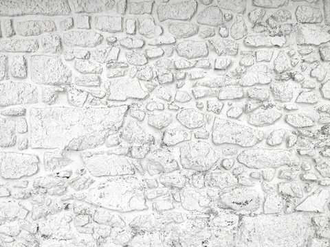 Old, whitewashed stone wall, painted white with peeling paint. Weathered background texture.