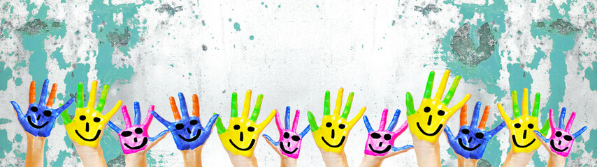 Obraz Many brightly painted children's hands with smileys, isolated on white background banner panorama with speckled spotted turquoise paint blobs, with space for text - fototapety do salonu