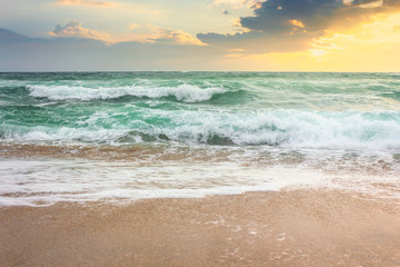 storm on the sandy beach at sunrise. dramatic ocean scenery with cloudy sky. rough water and crashing waves in morning light