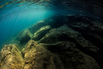 Fototapete - Sunlight and shadows mix underwater in the volcanic seafloor of Flores, Indonesia.