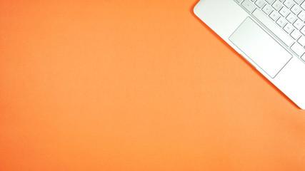 Personal pc laptop on bright color modern orange desktop overhead flatlay with negative copy space.