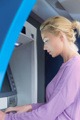 Young woman entering her pin code to withdraw money at ATM machine.