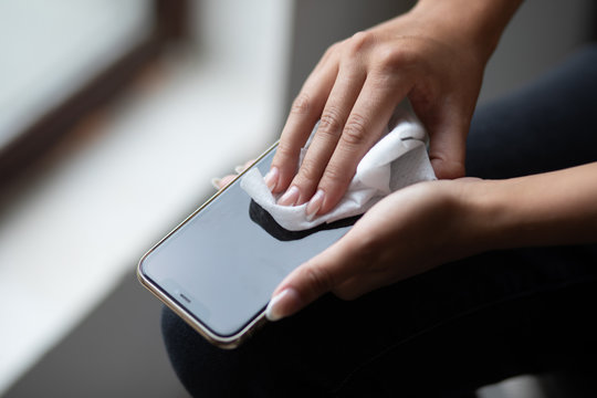 The woman cleans the cell phone with a wet wipes napkin stock photo