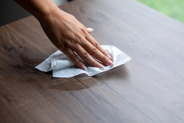 Woman cleaning home office table surface with wet wipes stock photo