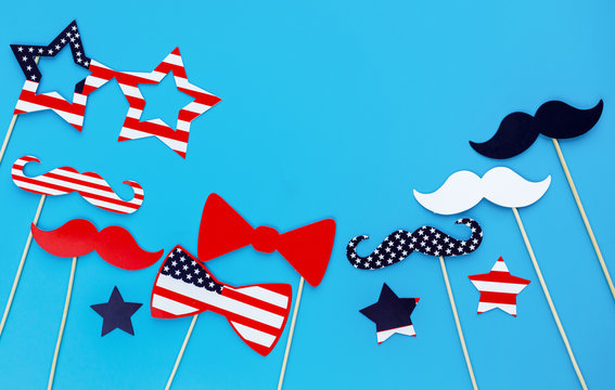 Photo booth for 4th of July. Moustaches, lips, glasses, hat on sticks on blue background. American flag colors. Independence Day, patriotic holiday background