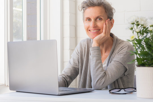 Close up of middle age woman with laptop smiling at camera - working from home concept (selective focus)