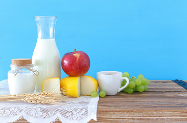 photo of dairy products over old wooden table and blue background. Symbols of jewish holiday -...