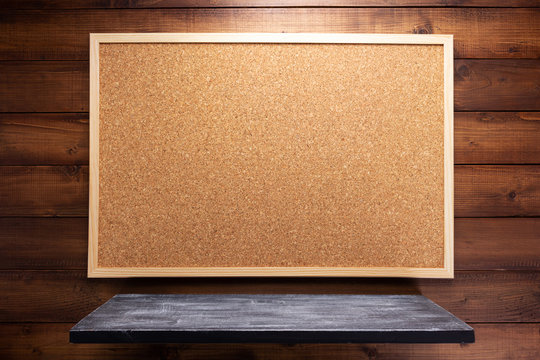 cork board and shelf on wooden background