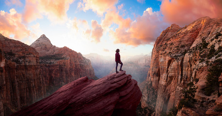 Adventurous Woman at the edge of a cliff is looking at a beautiful landscape view in the Canyon...