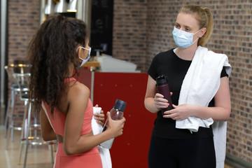 Zwei Frauen in Sportoutfits tragen einen Mundschutz und unterhalten sich