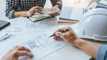 Fototapeta engineer Hand Drawing Plan On Blue Print with architect equipment discussing the floor plans over blueprint architectural plans at table in a modern office. obraz