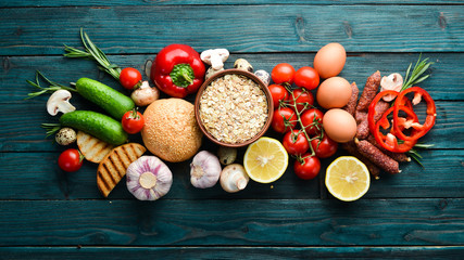 Fotomurales - Ingredients for breakfast: Eggs, oatmeal, sausages and fresh vegetables on a blue wooden background. Top view. Free space for your text.