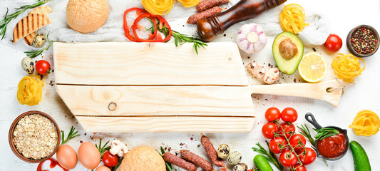 Fotomurales - White wooden food background: tomatoes, pasta, spices, vegetables and sausages. Top view.