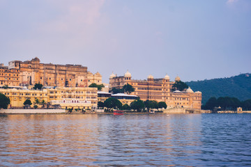 Fotomurales - View of famous romantic luxury Rajasthan indian tourist landmark - Udaipur City Palace on sunset with tourist boat. Udaipur, Rajasthan, India