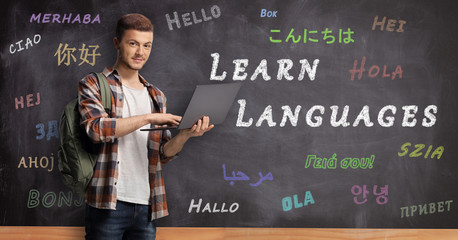 Male student with laptop standing in front of a blackboard with text learn languages