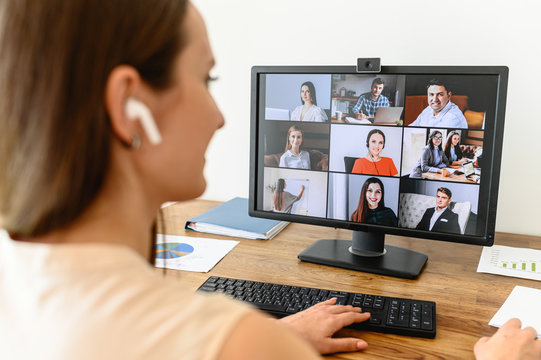 Video call, video meeting. A young woman connect with a many employees together via video, she sits at office space and looks at webcam, rear view