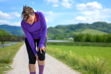 Woman jogger stopping to check an injured knee