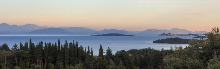 panoramic view of corfu town island mountains and sea with cypress and olive trees
