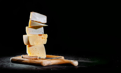 Different sorts of cheese. Сheese delicatessen on a black concrete background
