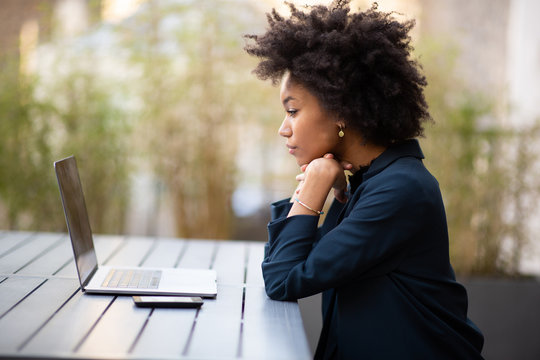 Side of young african american business woman sitting with laptop computer