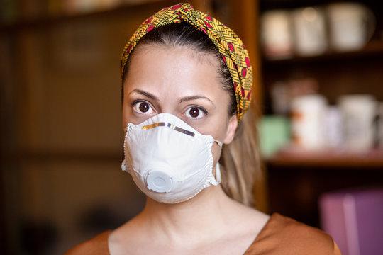 ritratto ambientato di un ragazza bianca che indossa una mascherina protettiva e una fascia per i capelli colorata