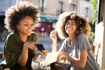 two happy female friends sitting at outdoor cafe with mobile phone
