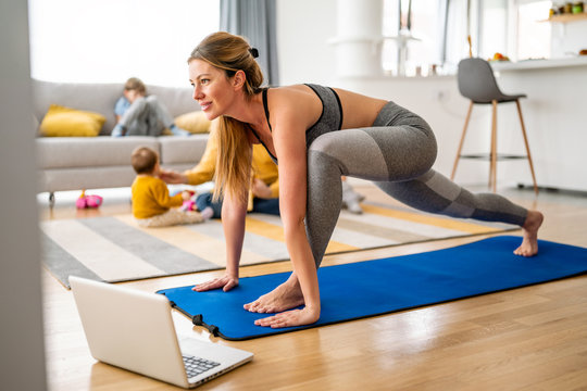 Young woman is exercising yoga at home. Fitness, workout, healthy living and diet concept.