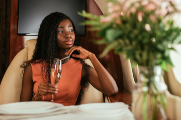 selective focus of dreamy african american woman holding glass of champagne in private jet