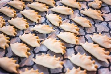 Traditional Polish home made dumplings on kitchen cloth - pierogi made of dough. Preparing meal at home. Pierogi ruskie, lots of raw dumplings