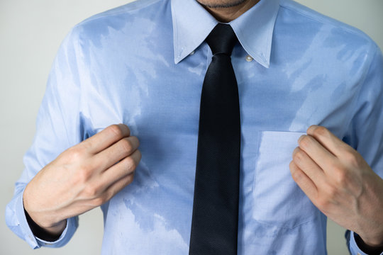 Sweating business man due to hot climate after work outdoor