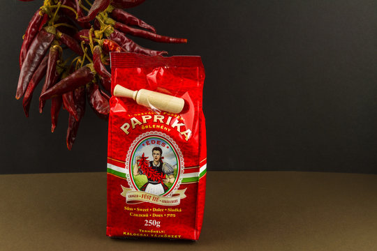 Illustrative editorial Chili-Trade Hungarian sweet smoked paprika, peppers in background, landscape